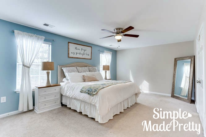 This blue master bedroom decor paint color is Sherwin Williams Rain and Sherwin Williams Accessible Beige. I love the furniture in this master bedroom on a budget. The side dressers hold their clothes so there is minimal furniture in the bedroom. This master bedroom looks like a relaxing retreat for couples.