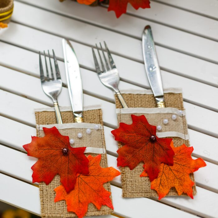 Dining utensils forks and knifes serving a wooden table decorated with autumn leaves, rowan berries, chestnuts, walnuts on a wooden background in rustic style