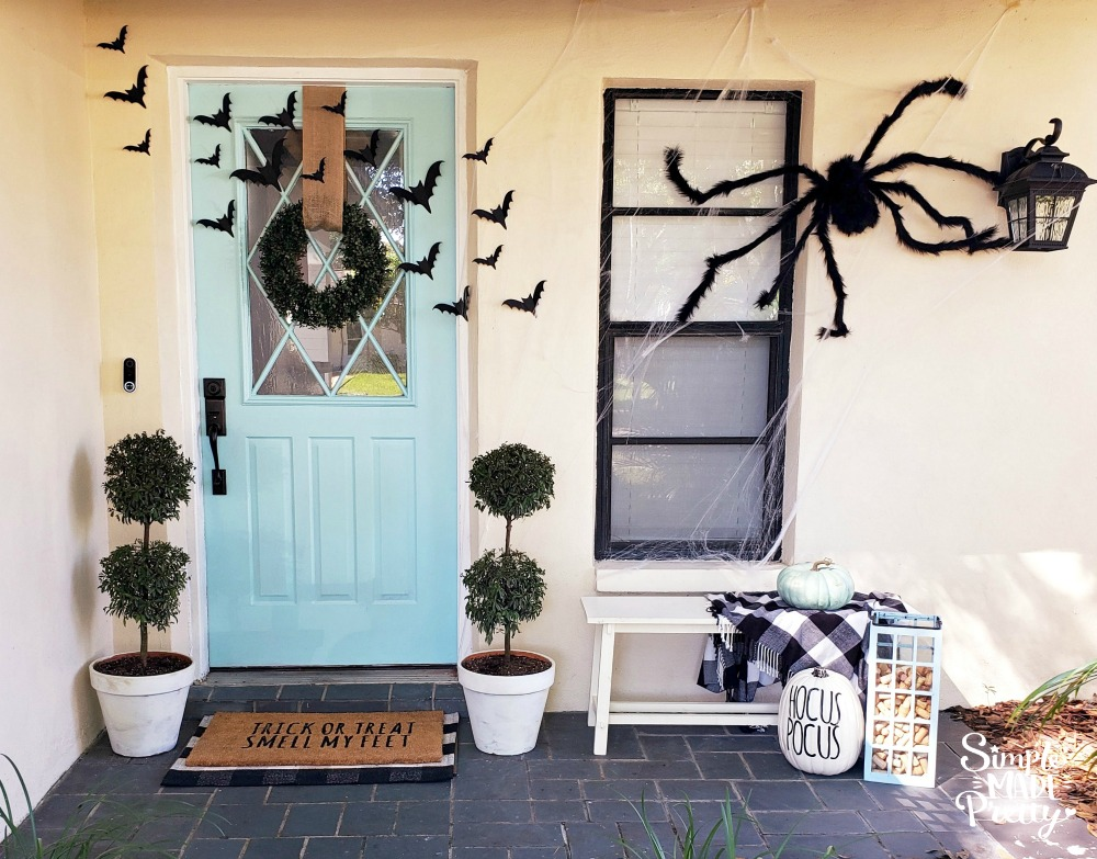 Keep your Halloween front door decorations simple this year while creating spooky Halloween decorations for your Fall front door.  These are creative ideas for homemade Halloween decor that's also cheap Halloween decor and goes with a teal blue front door. The result is Simple Halloween Front Porch Decor that adds the perfect touch of Halloween outdoor decorations. Keep reading for how I updated our Fall front door decorations in under an hour! #halloweenfrontporchdecor #DIYHalloweendecor